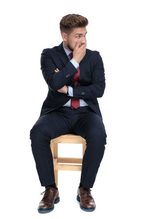 shocked young businessman, covering mouth with hand, looking to side and sitting isolated on white background in studio