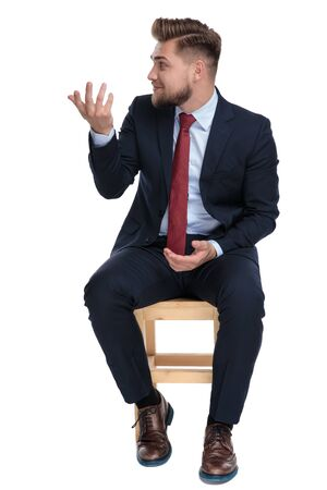 confused young businessman looking to side, gesticulating and sitting isolated on white background in studio