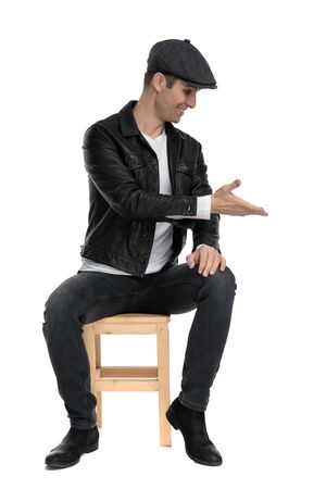 good looking casual man wearing a black leather jacket and hat sitting and presenting to a side happy while looking down against white studio background