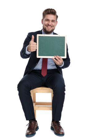 happy young businessman smiling, holding empty blackboard and making thumbs up sign, sitting isolated on white background in studio