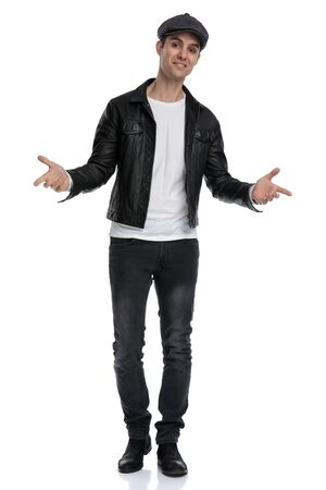 good looking casual man wearing a black leather jacket and hat standing with open arms and looking ahead cocky against white studio background Stockfoto