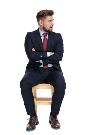 shocked young businessman folding arms, looking to side and sitting isolated on white background in studio Фото со стока