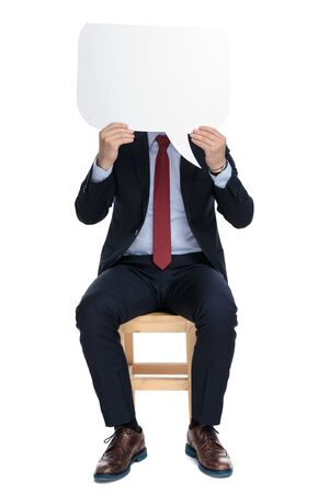 young businessman holding speech bubble and hiding behind it, sitting isoalted on white background in studio 版權商用圖片 - 130803306