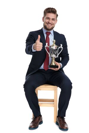 happy young businessman smiling, holding tropy and making thumbs up sign, sitting isolated on white background in studio Reklamní fotografie