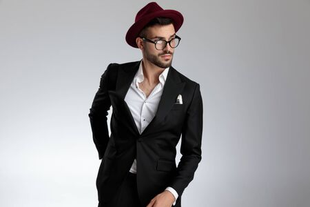 brunet formal business man wearing a black suit,hat,glasses is standing with one hand behind him and looking away pensive on gray studio background