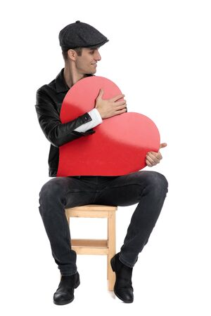 young casual man wearing a black leather jacket and hat sitting and holding his big red heart tight while looking to a side happy against white studio background Imagens