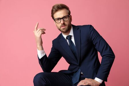 good looking formal business man in navy suit and glasses is sitting and resting his hands on his laps while looking at camera intrigued on pink studio background