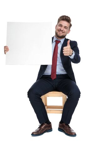 happy young businessman smiling, holding empty white board and making thumbs up sign, sitting isolated on white background in studio