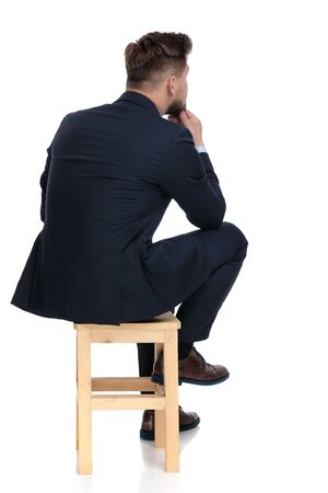 back view of young businessman holding hands to chin, thinking, sitting isolated on white background in studio