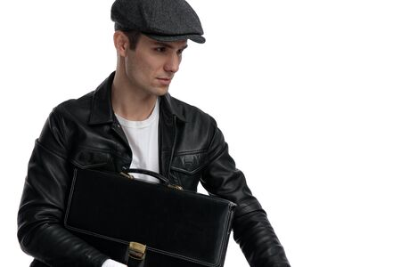 portrait of a fine casual man wearing a black leather jacket and hat sitting and holding a briefcase while looking away pensive against white studio background