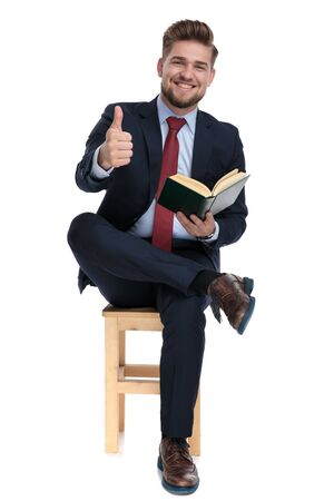 happy young businessman holding book, smiling and making thumbs up sign, sitting isolated on white background in studio Reklamní fotografie
