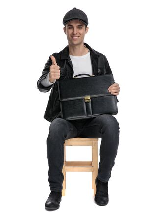 attractive casual man wearing a black leather jacket and hat sitting and holding a briefcase while making a ok sign gesture confident against white studio background Reklamní fotografie