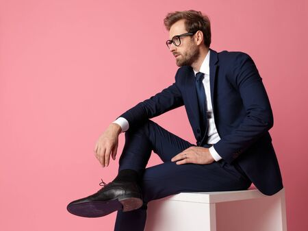 side view of a young formal business man in navy suit with glasses  sitting and resting his hands on his laps and his leg on the chair while looking away pensive on pink studio background Stock Photo