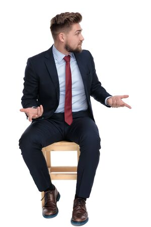 confused young businessman looking to side, holding hands and gesticulating, talking, sitting isolated on white background in studio