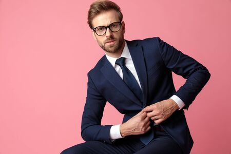 beautiful formal business man wearing a navy suit and glasses is sitting and holding his jackets button while  looking at camera serious on pink studio background Stock Photo