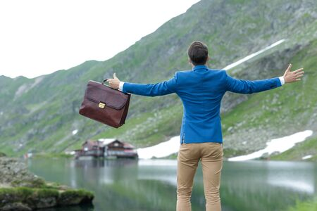 back view of smart casual man wearing blue coat, holding suit case, opening arms and embracing the nature, outdoor at Balea Lake, Romania Stock Photo