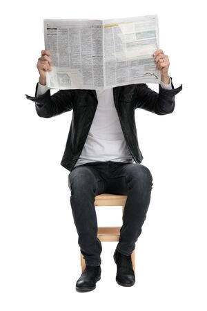 handsome casual man wearing a black leather jacket and hat sitting and covering his face with a newspaper against white studio background