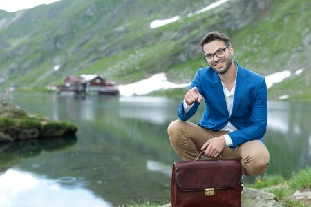 smart casual man wearing blue jacket, pointing finger and smiling, holding suitcase, outdoor in nature at Balea Lake, Romania