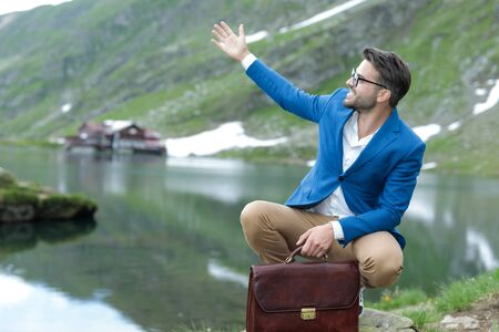 enthusiastic smart casual man wearing blue jacket, holding suitcase, presenting nature with enthusiasm, outdoor at Balea Lake, Romania