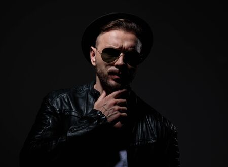 cool biker wearing leather jacket, sunglasses and hat, holding hand to chin and thinking, on grey background in studio Stok Fotoğraf