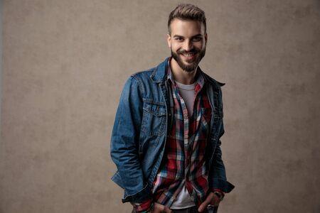 gelukkige casual man met een blauw spijkerjack, glimlachend en hand in hand in de zakken, op een bruine achtergrond in de studio