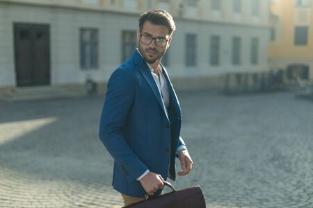 side view of arrogant smart casual man, wearing blue coat, holding suitcase and looking to side, outdoor in an urban scene