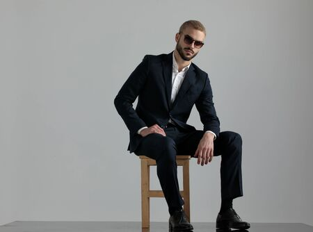 charming formal business man wearing a navy suit and sunglasses sitting on a chair resting his hands and looking at camera serious on gray studio background