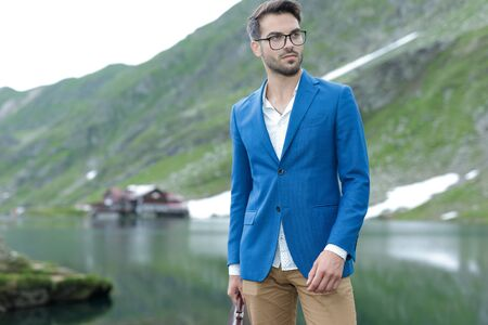 smart casual fashion model wearing blue jacket, looking to side and admiring,and holding suitcase, outdoor in nature at Balea Lake, Romania