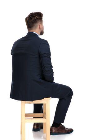 Vue arrière du jeune homme d'affaires pensant, assis isolé sur fond blanc en studio Banque d'images
