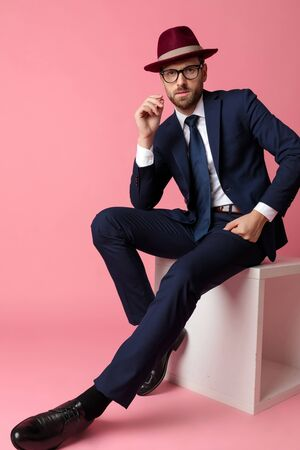 mysterious  formal business man wearing a navy suit,burgundy hat,glasses  sitting and resting his hands on his laps while looking at camera serious  on pink studio background