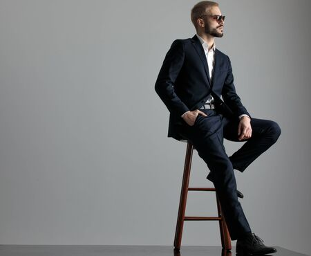 side view of a handsome formal business man wearing a navy suit and sunglasses sitting with one leg resting on a chair and one hand in pocket while looking ahead confident