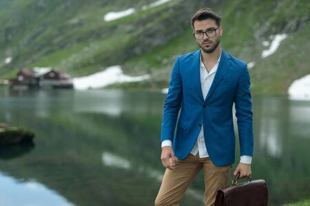 smart casual fashion model wearing blue coat, holding suitcase, standing outdoor in nature at Balea Lake, Romania Stock Photo