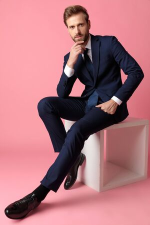 young formal business man in navy suit is sitting and resting his hands on his laps while touching his chin and looking at camera pensive on pink studio background