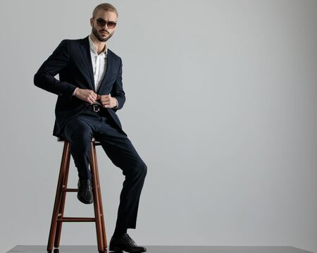 elegant formal business man wearing a navy suit and sunglasses sitting with one leg resting on a chair and holding his jackets button while looking at camera confident on gray studio background