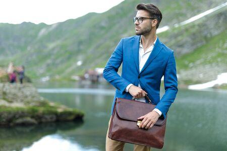 Smart Casual Mann mit blauem Mantel, Koffer halten und zur Seite schauen, im Freien in der Natur, am Balea-See, Rumänien