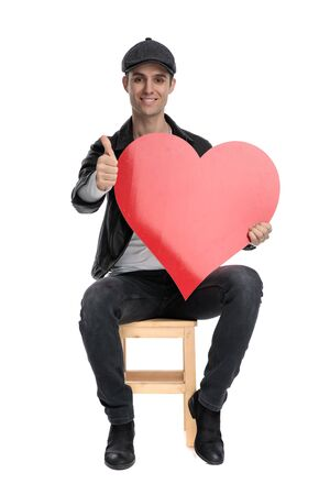 gorgeous casual man wearing a black leather jacket and hat sitting and holding a big red heart while making a ok sign against white studio background
