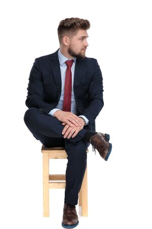 impatient young businessman looking to side and waiting, sitting isolated on white background in studio