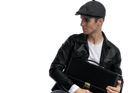 portrait of a young casual man wearing a black leather jacket and hat sitting and holding a briefcase while looking to a side curious against white studio background