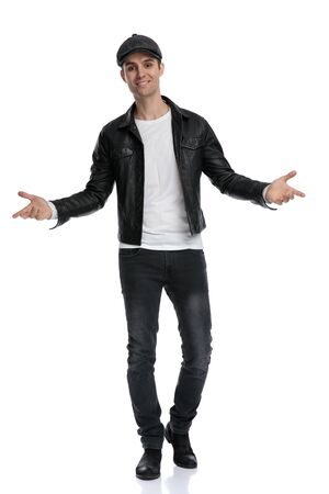 fine casual man wearing a black leather jacket and hat standing and greeting with open arms happy against white studio background Stockfoto