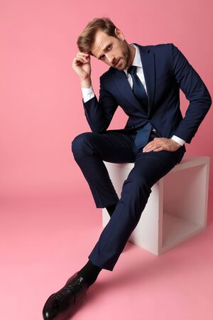 attractive formal business man in navy suit is sitting and resting his hands on his laps and his head on one hand while looking at camera serious on pink studio background Stock Photo