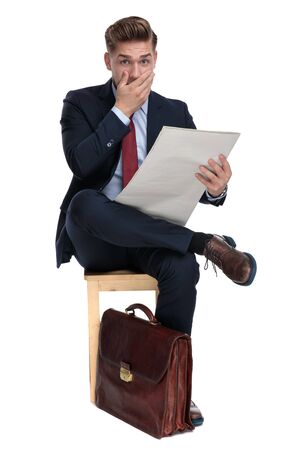 shocked young businessman reading newspaper and holding hand to mouth, sitting isoalted on white background in studio