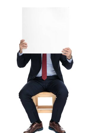 young businessman hiding behind empty white board, sitting isolated on white background in studio
