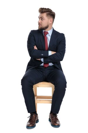 shocked young businessman looking to side, folding arms and sitting isolated on white background in studio