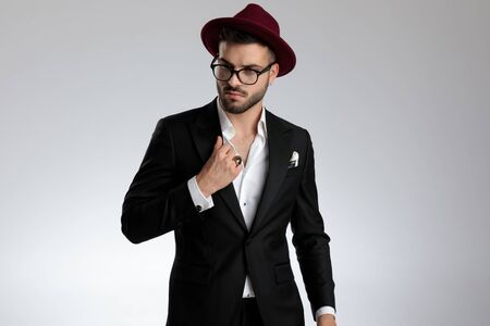 sexy formal business man wearing a black suit,hat,glasses,ring is standing and looking away pensive while fixing collar on gray studio background