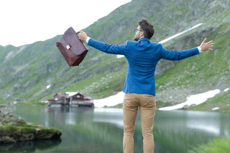 back view of smart casual man wearing blue coat, holding suitcase, holding arms open and feeling free, outdoor in nature, at Balea Lake, Romania