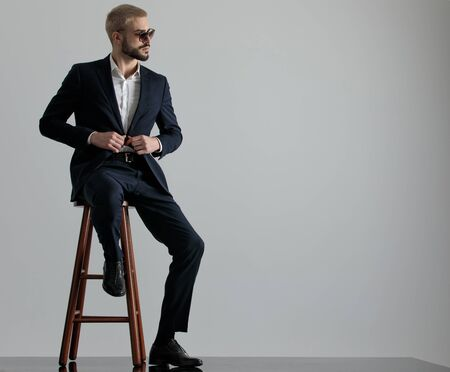 elegant formal business man wearing a navy suit and sunglasses sitting with one leg resting on a chair and holding his jackets button while looking to a side confident on gray studio background Stock Photo