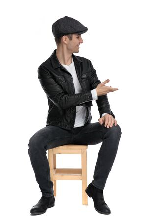 beautiful casual man wearing a black leather jacket and hat sitting and greeting to a side happy against white studio background