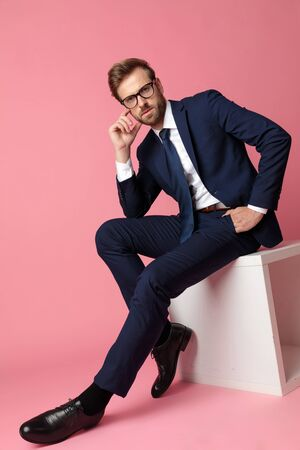 side view of an attractive  formal business man in navy suit with glasses sitting and resting his hands on his laps while touching his face and looking at camera serious on pink studio background