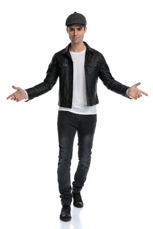 charming casual man wearing a black leather jacket and hat walking with open arms intrigued against white studio background Stockfoto