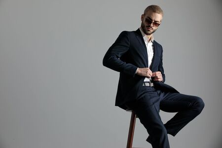 side view of a young formal business man wearing a navy suit and sunglasses sitting with one leg resting on a chair and holding his hands on his jackets button while looking down sad on gray studio background